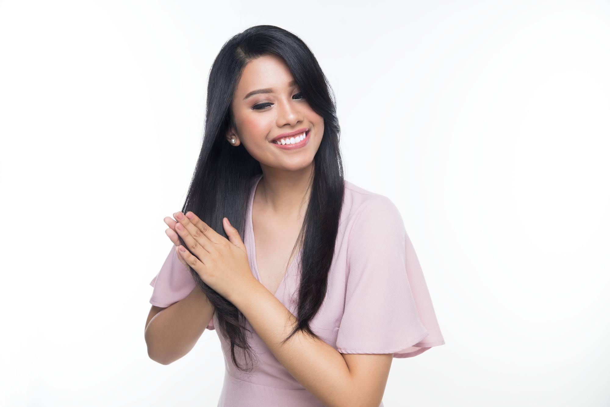Wanita Asia berambut panjang lurus mengusapkan vitamin pada ujung rambut.
