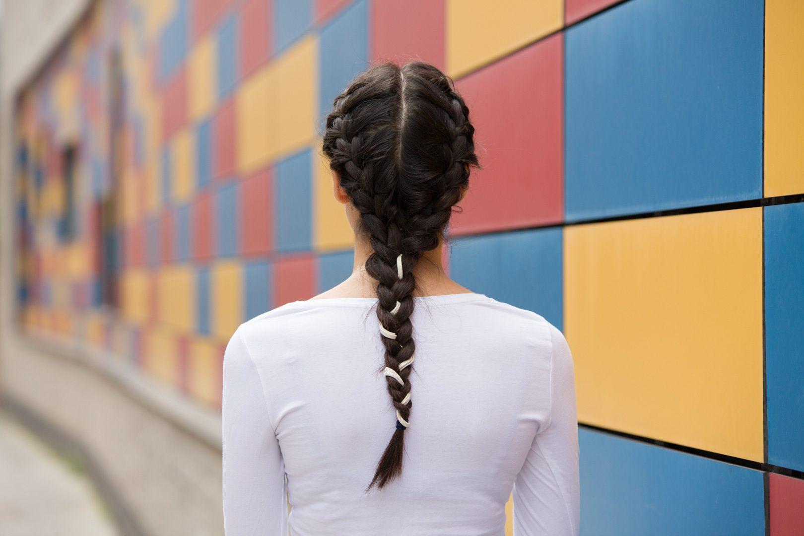 Wanita kaukasia dengan rambut hitam gelap dan gaya rambut double french braids menghadap ke belakang