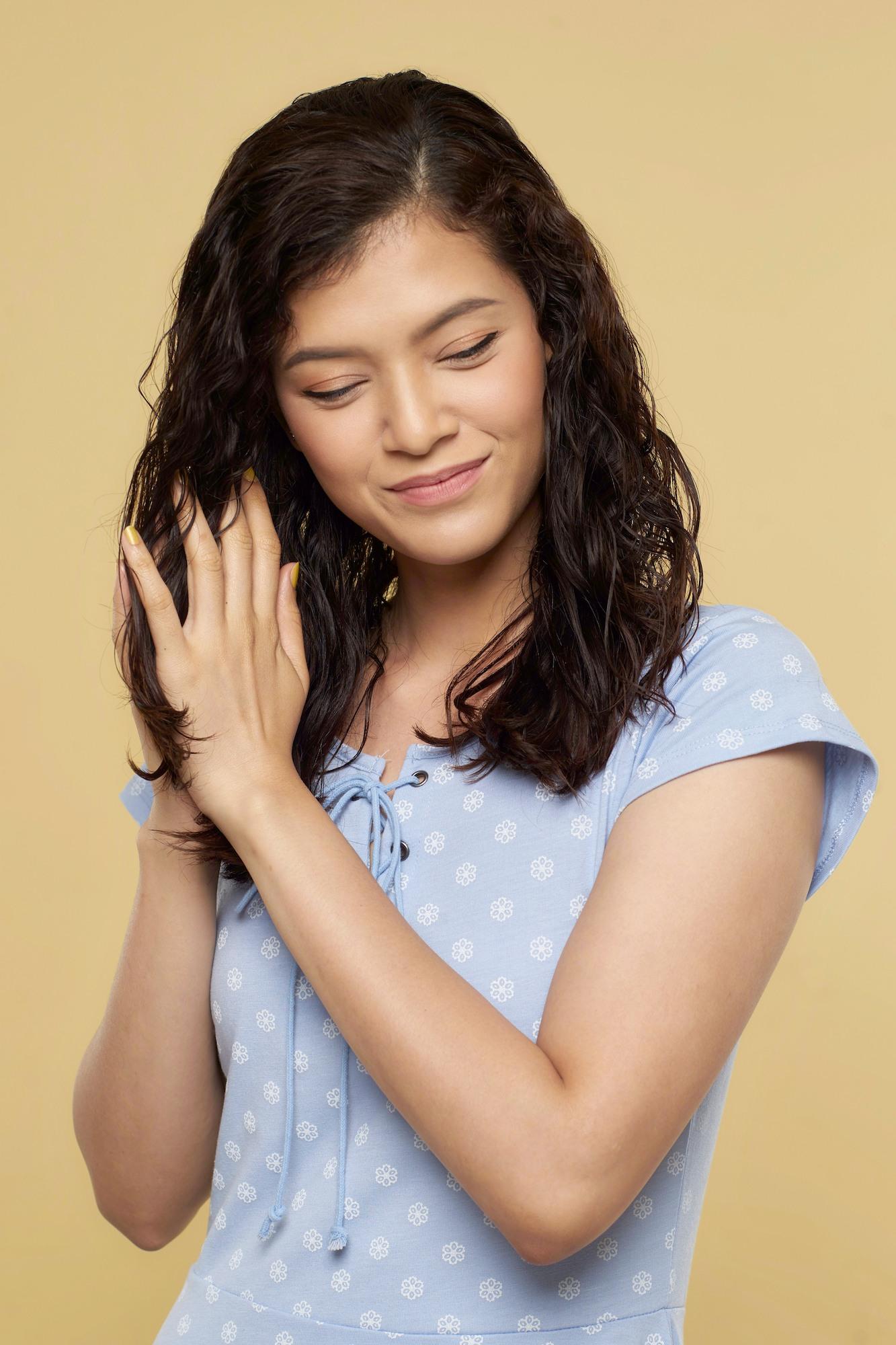Wanita asia memegang rambut basahnya, model rambut pendek keriting - Cara menghilangkan ketombe secara alami