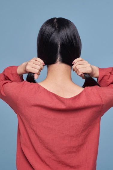 Cara menghilangkan ketombe secara alami - wanita asia membelah rambutnya menjadi dua menggunakan baju warna pink
