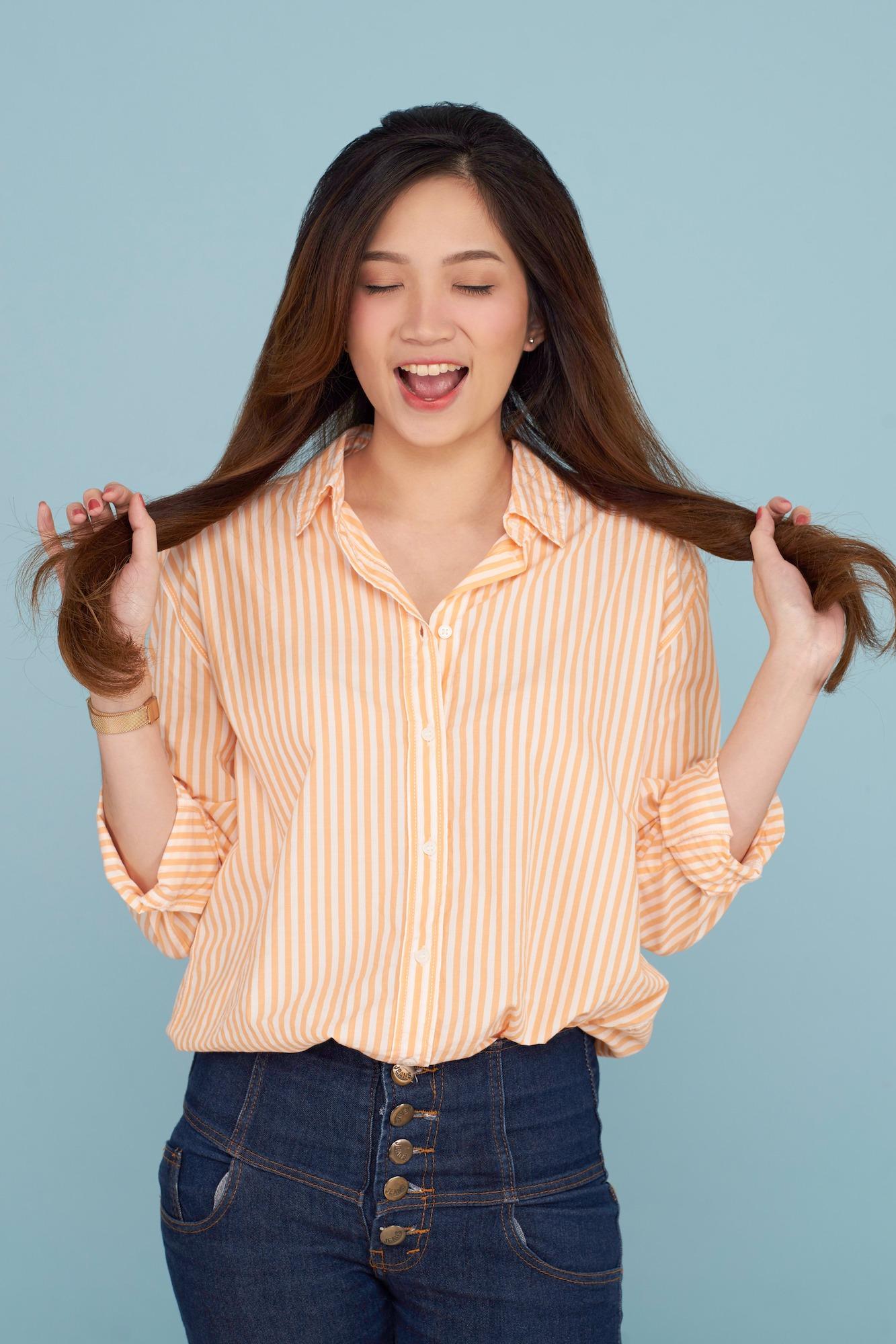 Wanita asia memegang kedua belahan rambut dan memainkan rambut - cara menghilangkan ketombe secara alami