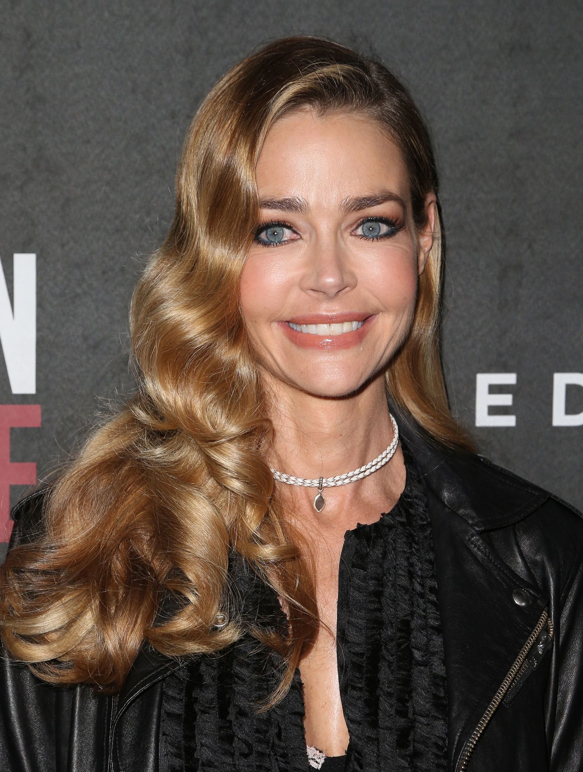 Denise Richards dengan model rambut Hollywood curls warna pirang gelap.
