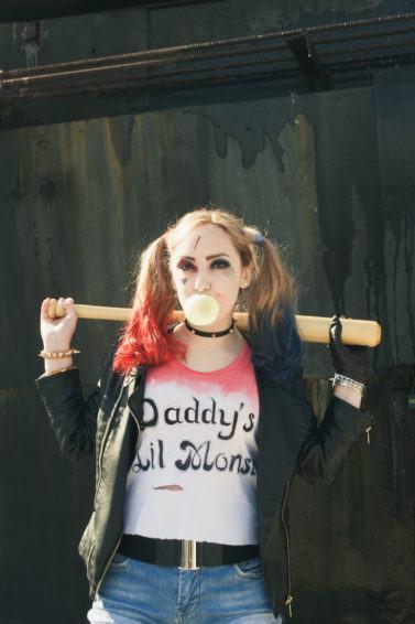 Wanita kaukasia dengan cosplay kostum Harley Quinn, rambut double ponytail ombre merah dan biru.