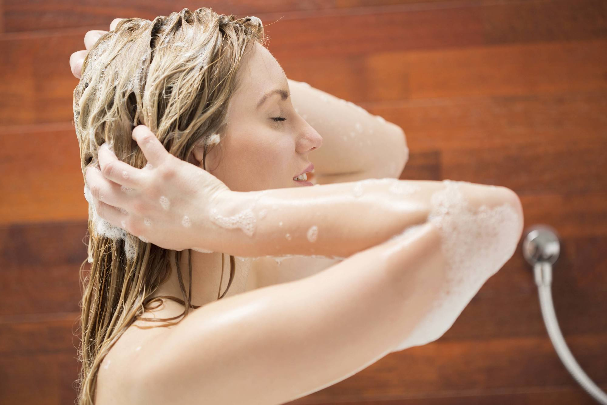 Wanita kaukasia mencuci rambutnya saat mandi