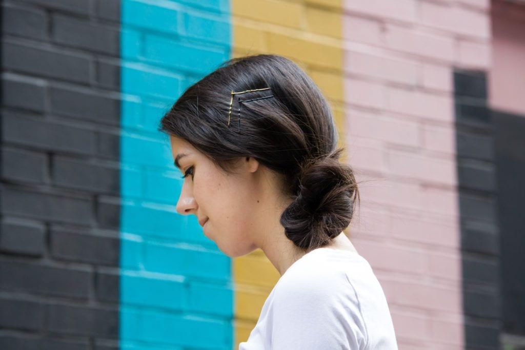 Wanita kaukasia dengan warna rambut hitam gaya rambut side bun dengan jepit