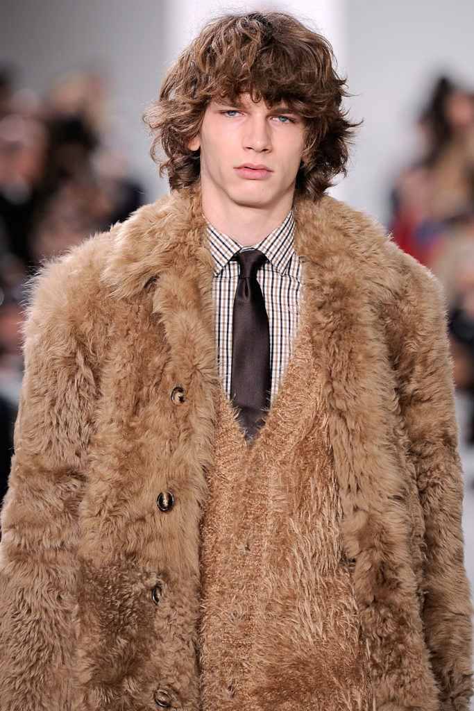 Pria kaukasia dengan model rambut keriting panjang cokelat gelap menggunakan jaket bulu warna cokelat