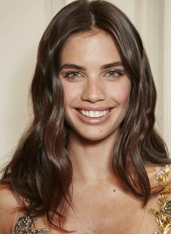 Wanita kaukasia dengan wajah oval berambut panjang layer yang sesuai dengan bentuk wajah oval
