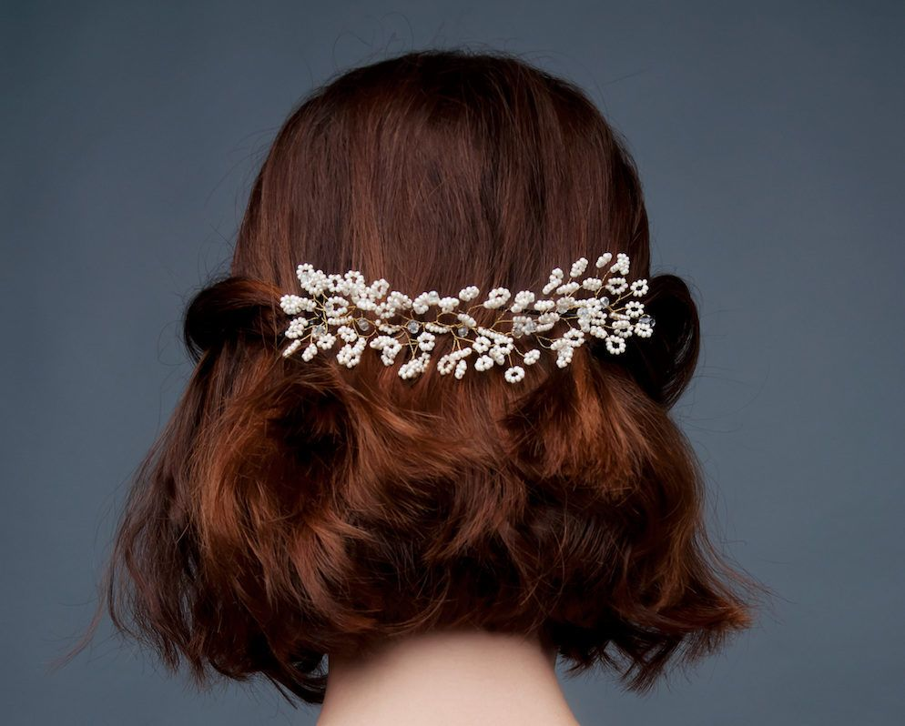 Wanita dengan rambut cokelat dan rambut half updo dengan aksesoris