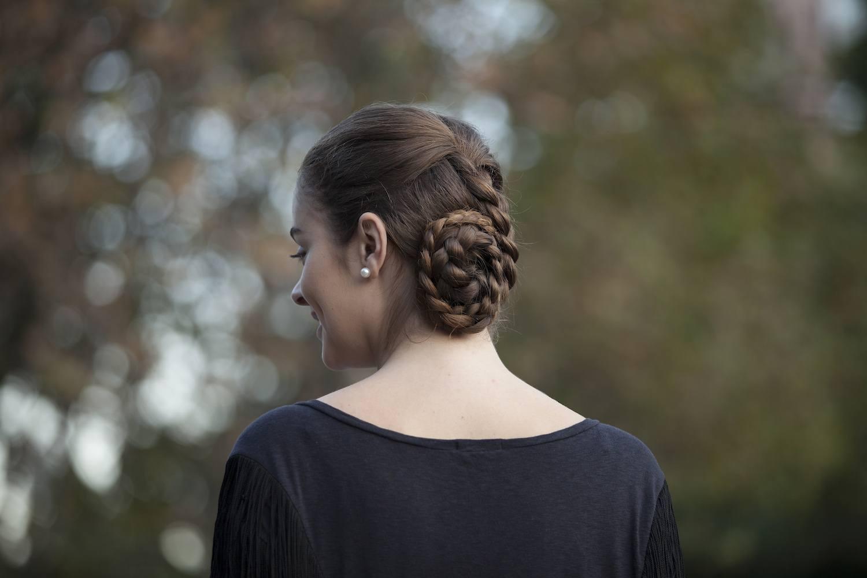 Wanita dengan rambut cokelat yang ditata dengan model sanggul variasi chignon dengan kepang.