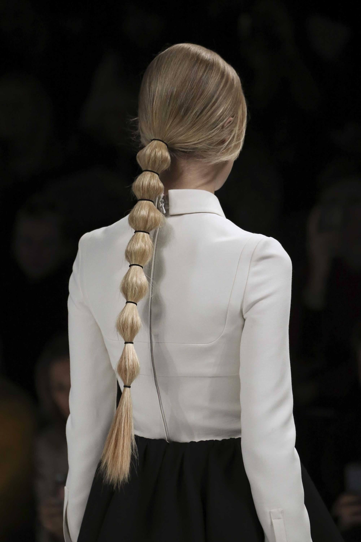 Wanita rambut pirang yang dikuncir dengan gaya bubble ponytail.