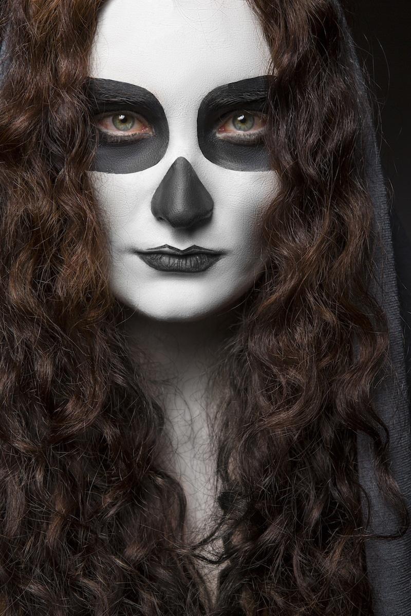 Wanita kaukasia dengan makeup tengkorak dan rambut keriting untuk Halloween