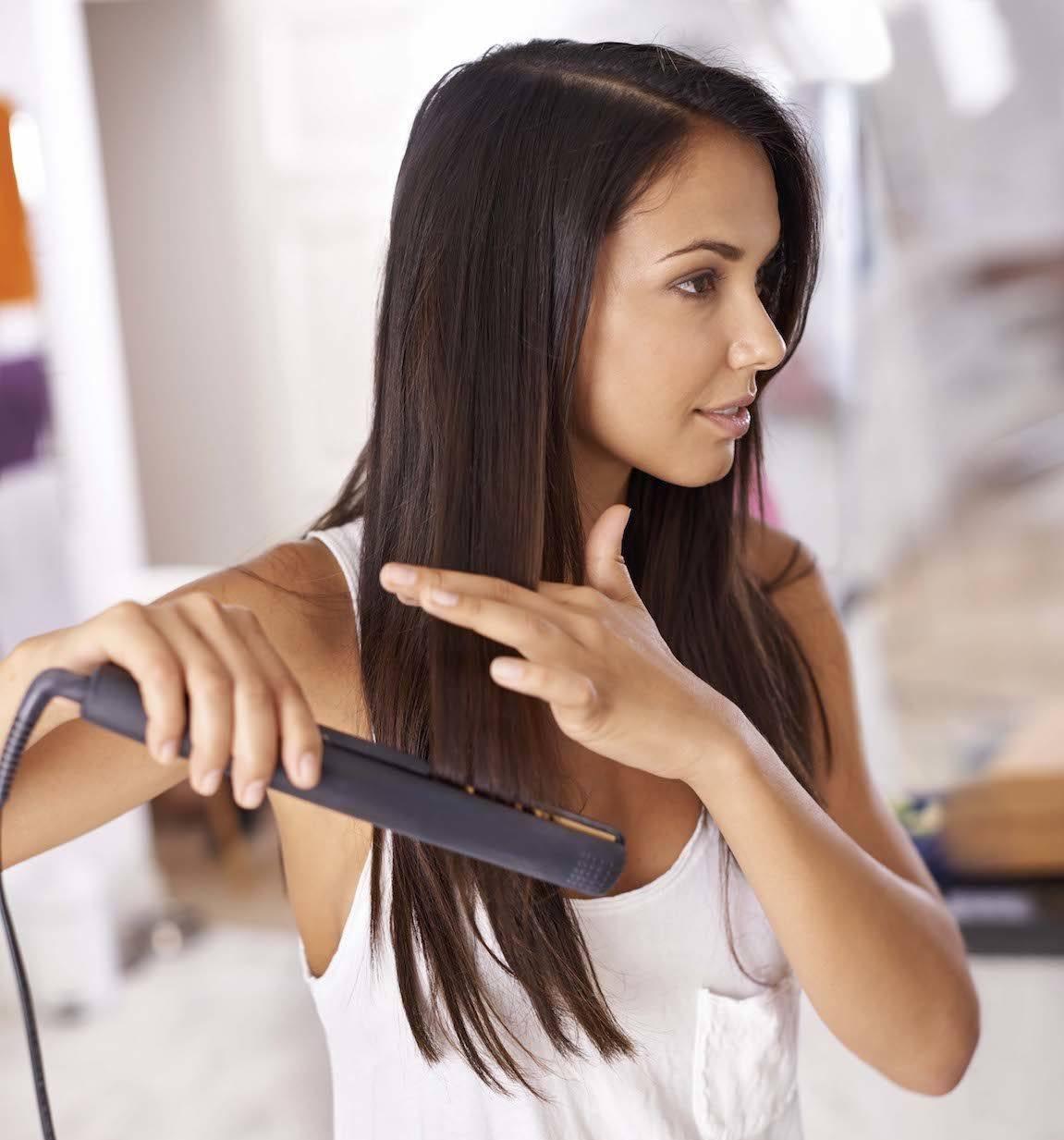 Perempuan kaukasia dengan rambut cokelat menggunakan flat iron