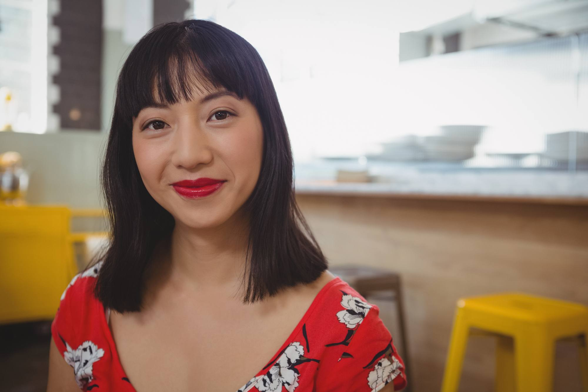 Cara mengatasi rambut berminyak pada wanita asia dengan rambut hitam model rambut bob sebahu dengan poni tersenyum menatap kamera