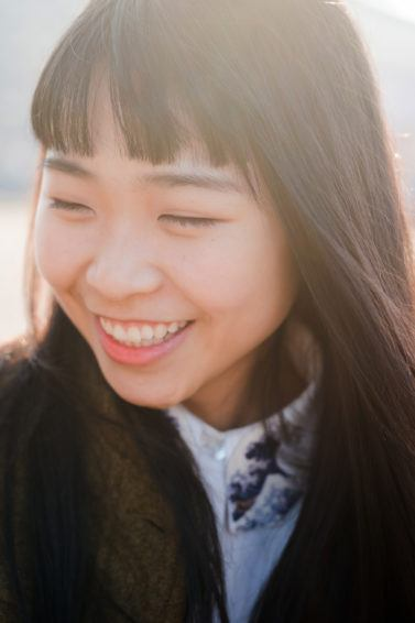 Perempuan asia dengan poni tersenyum ke arah samping