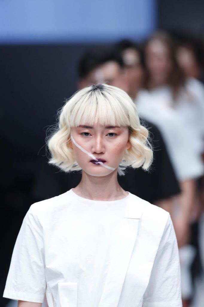 Wanita asia dengan model rambut bob pendek wavy warna platinum blonde.