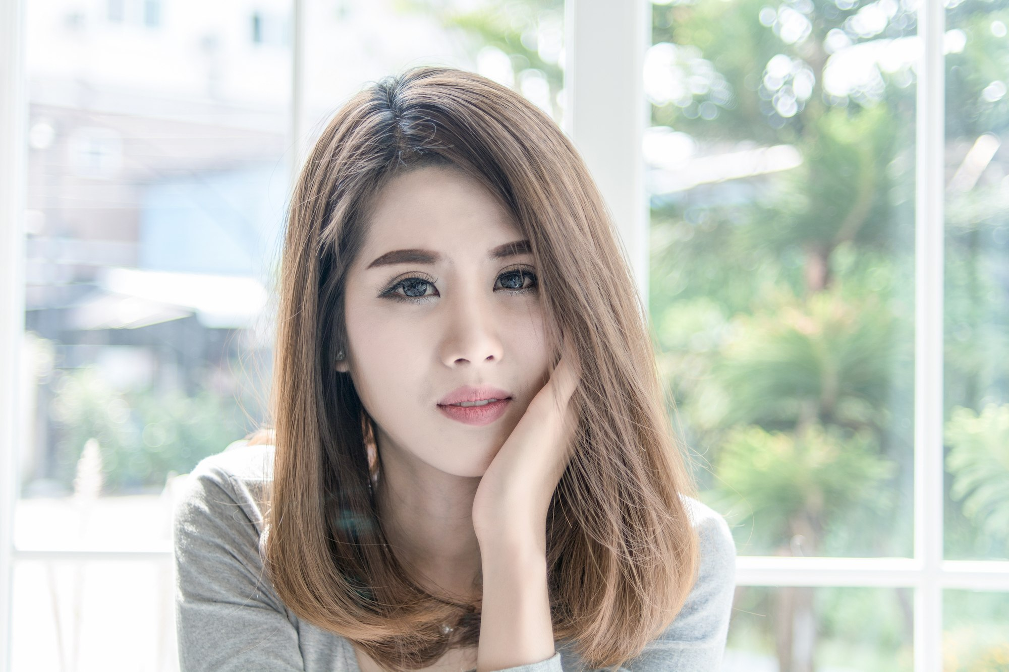 Wanita Asia dengan model bob sebahu lurus warna ash brown.