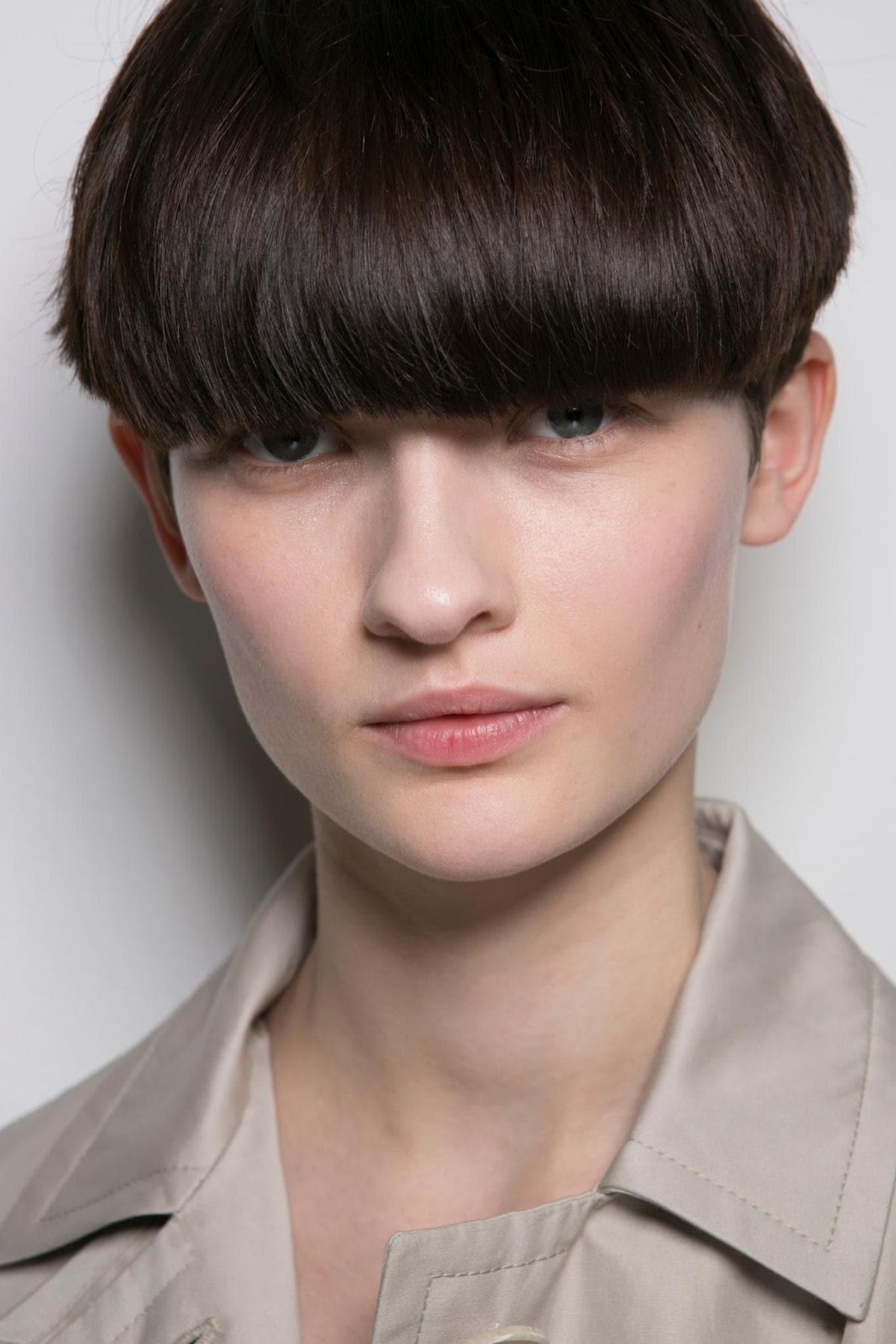 Wanita kaukasia dengan model rambut bowl cut gaya androgini