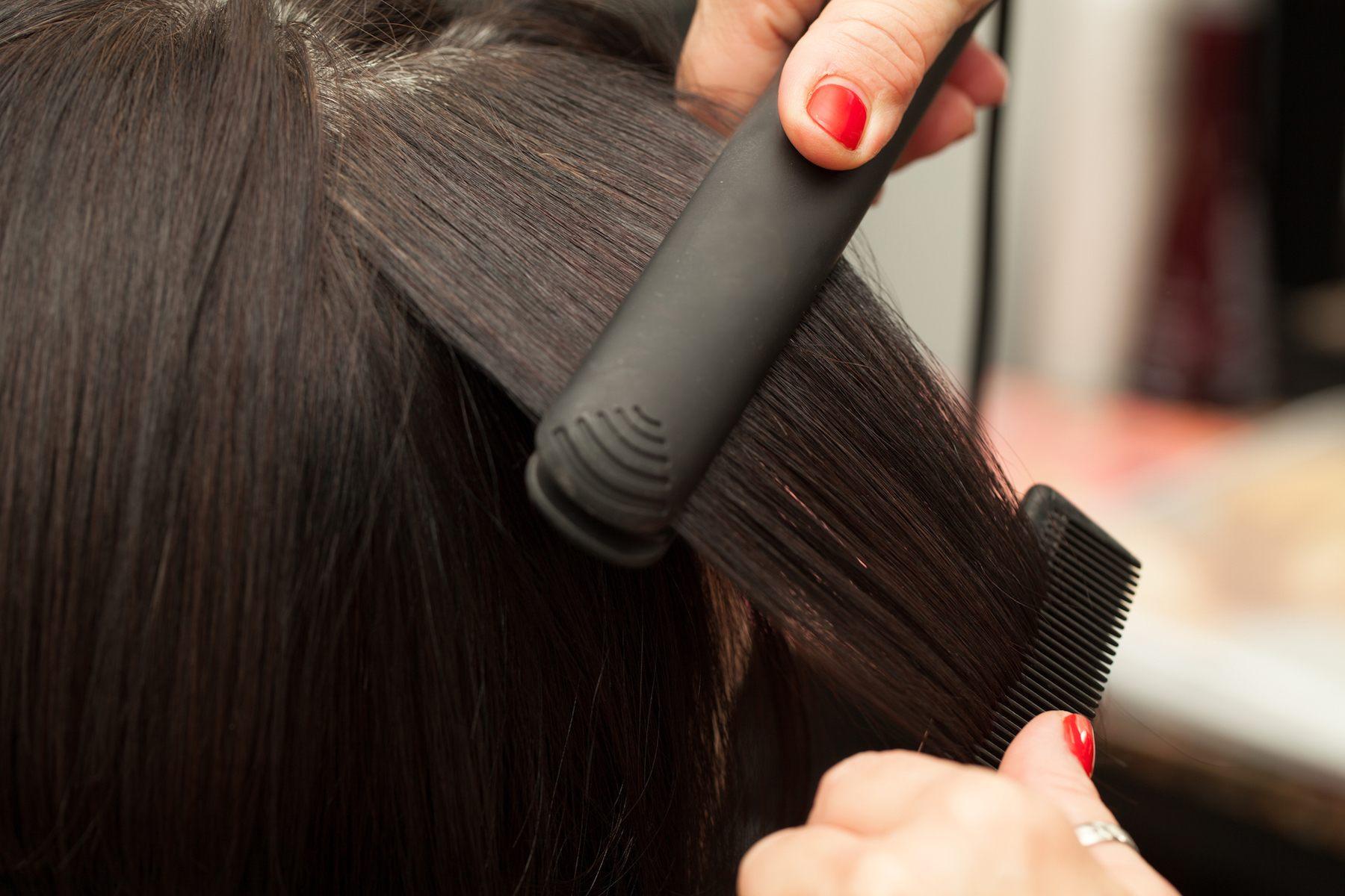 Mencatok rambut dengan flat iron untuk mendapatkan model rambut rebonding