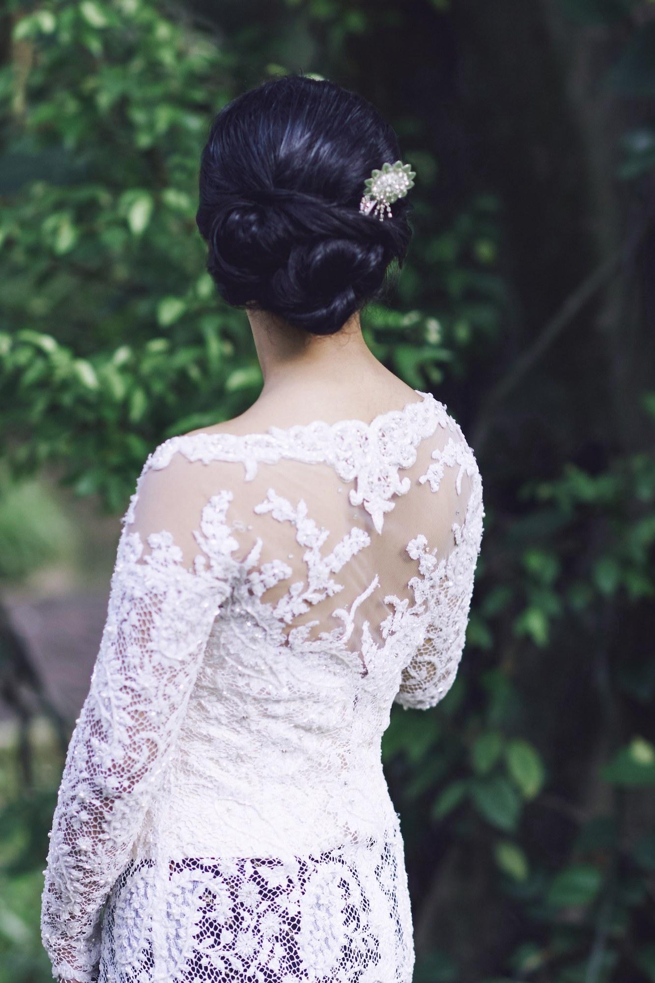 Wanita asia dengan rambut hitam dan model rambut kebaya menggunakan kebaya dengan aksesoris bunga