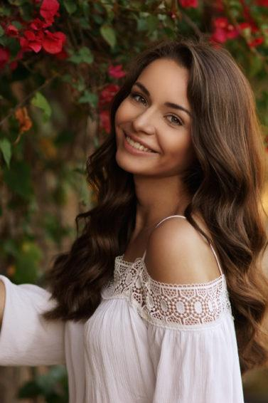 Wanita Asia dengan rambut panjang bergelombang warna cokelat medium.