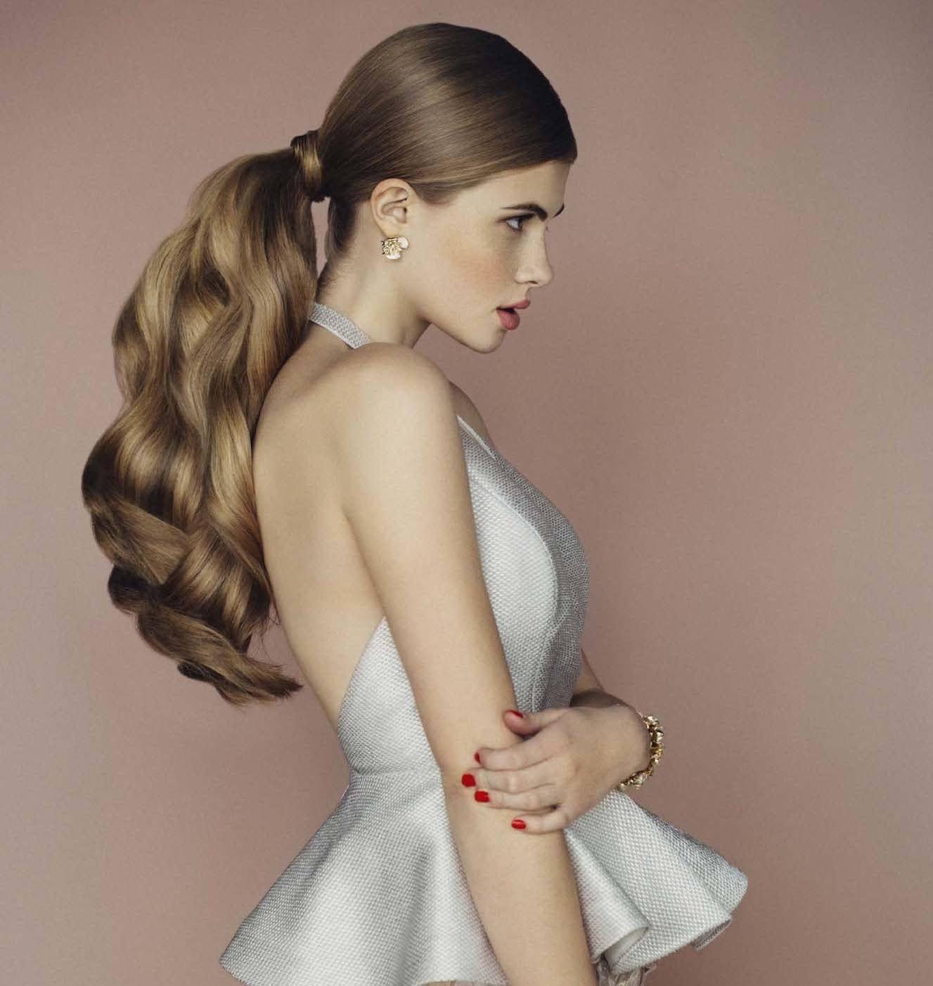 Cara menata rambut panjang untuk pesta gaya ponytail ikal.