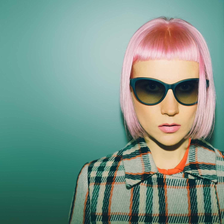 Warna rambut pastel pink padukan dengan model rambut gaya poni mikro.