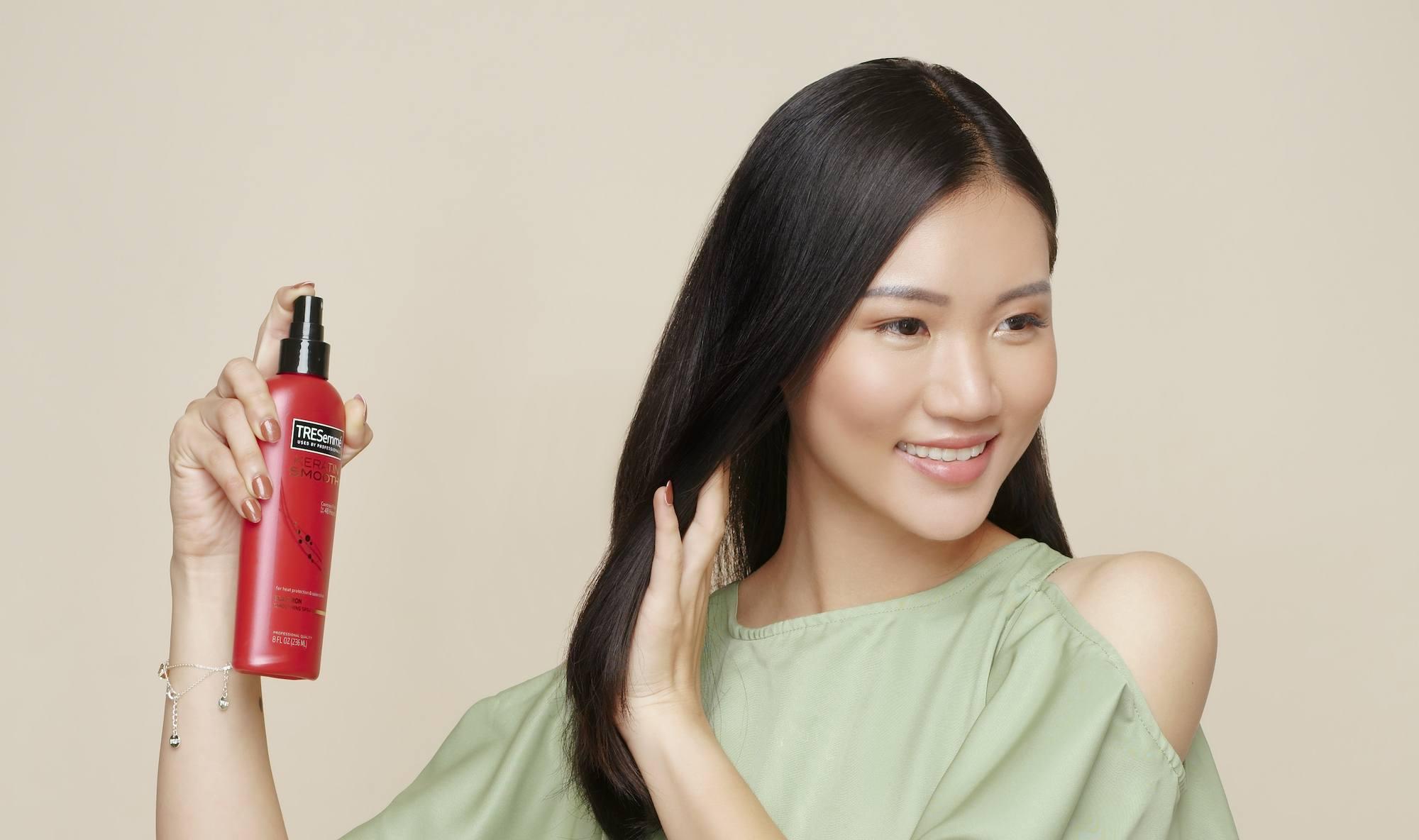 Wanita Indonesia menggunakan spray rambut