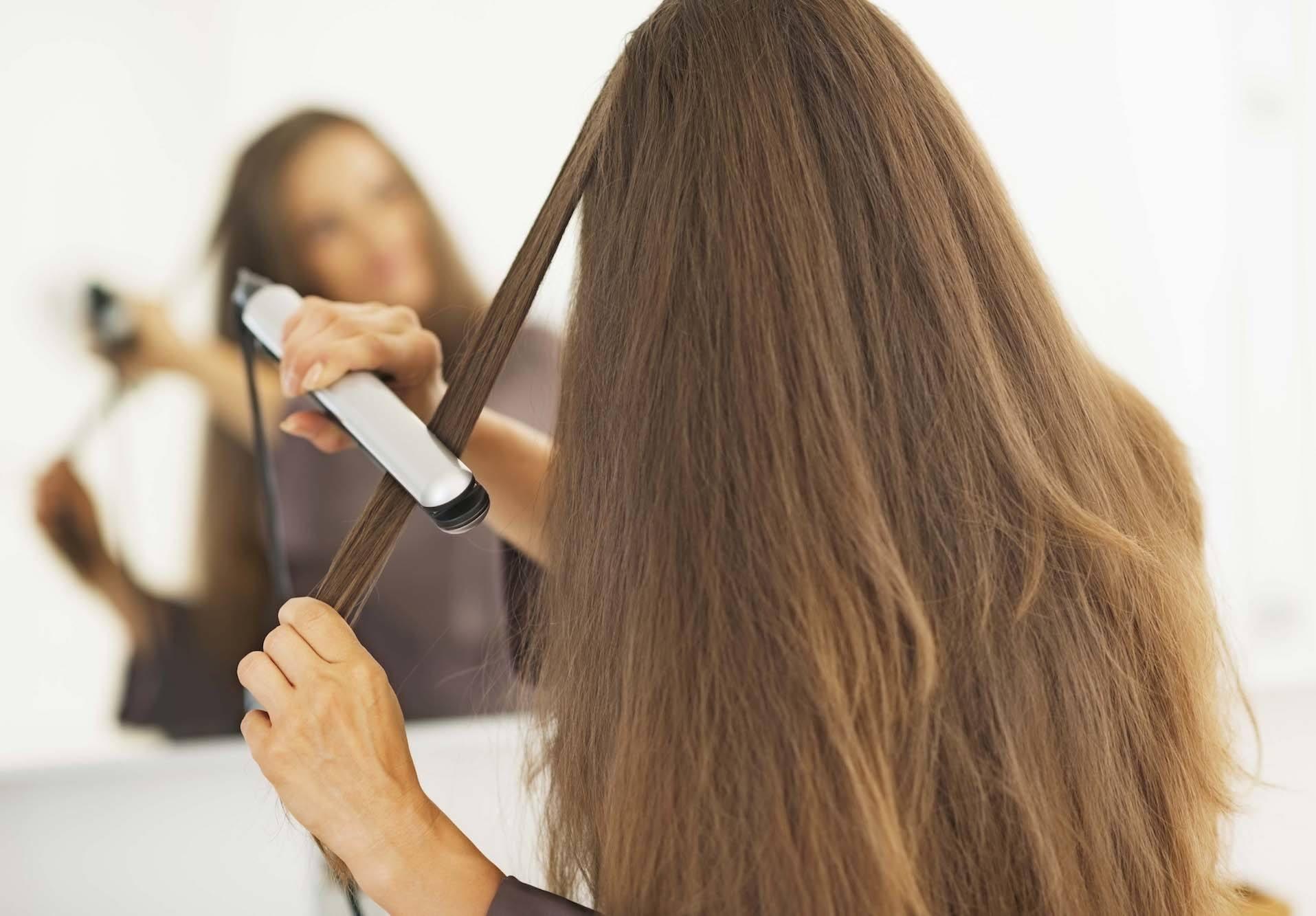 Seorang wanita mencatok rambutnya warna cokelat