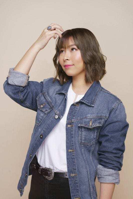Wanita asia dengan warna rambut pendek ash brown menggunakan jaket jeans dan baju dalam putih