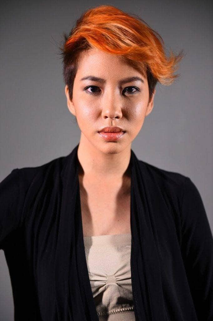 Wanita asia dengan warna rambut pendek oranye kekuningan dan menggunakan baju warna hitam