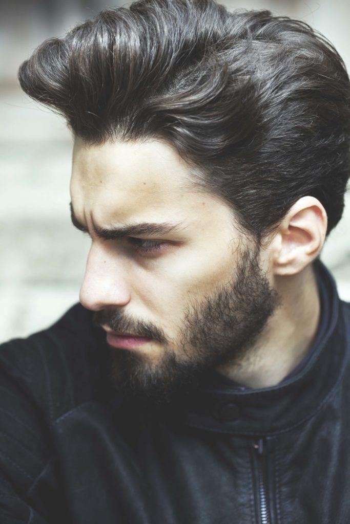 Model rambut pria bergelombang gaya clean cut dan belah pinggir.
