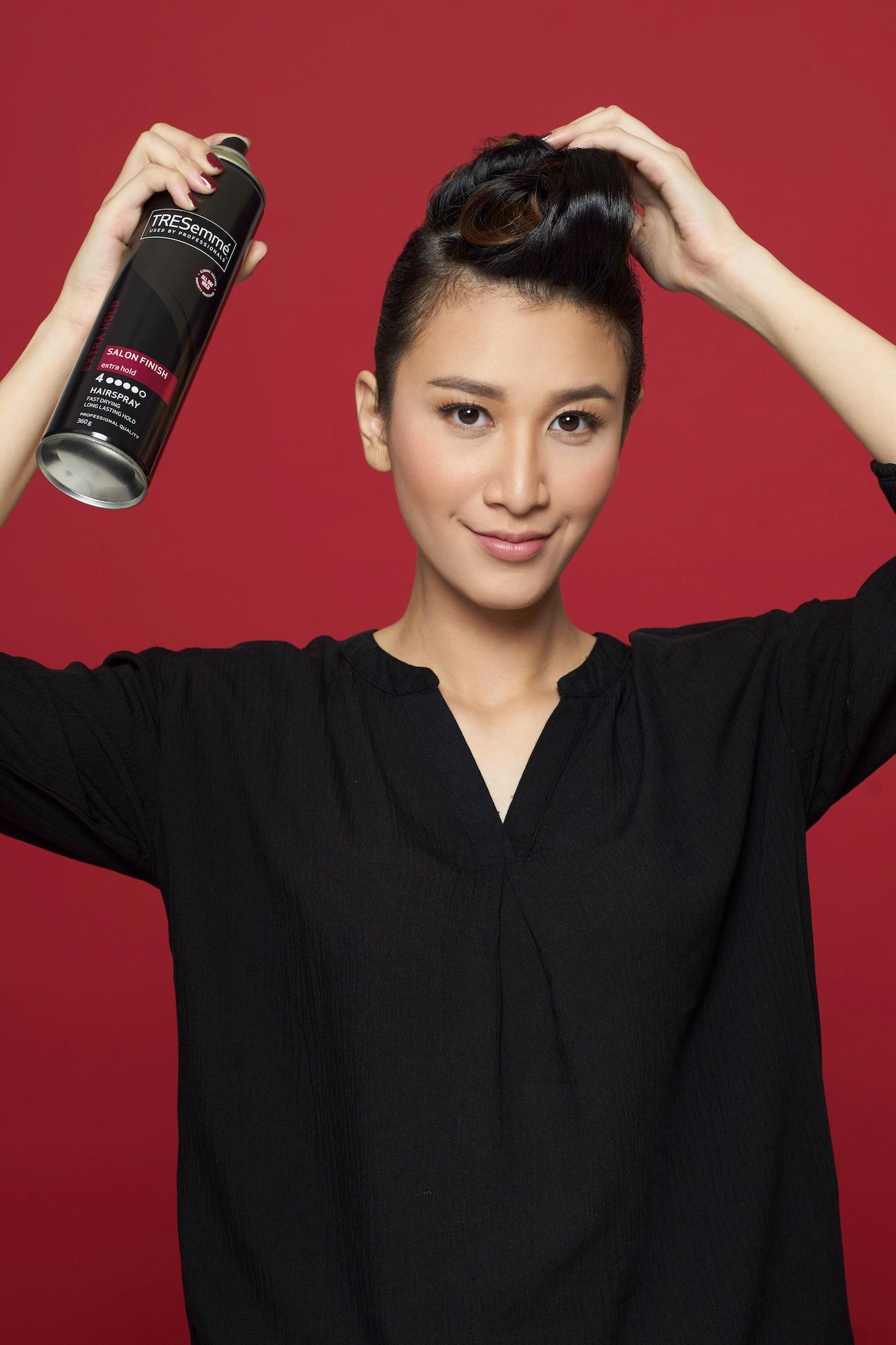 Wanita asia menggunakan spray rambut