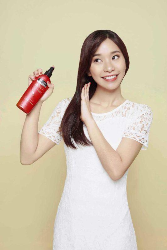 Wanita asia dengan rambut hitam menggunakan TRESemmé Keratin Smooth Flat Iron Smoothing Spray