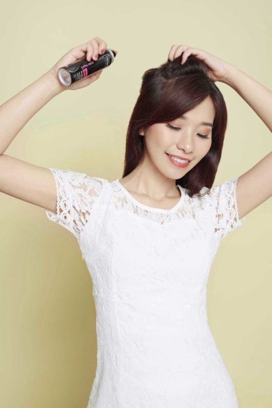 Wanita asia dengan rambut hitam panjang menyemprotkan TRESemmé Extra Hold Hair Spray pada rambut hitam panjangnya.