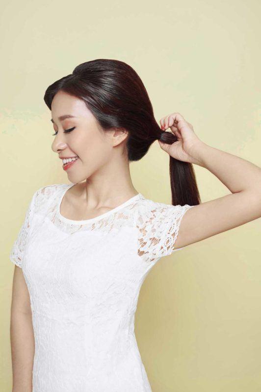 Wanita asia dengan rambut warna hitam mengikat rambut model ponytail