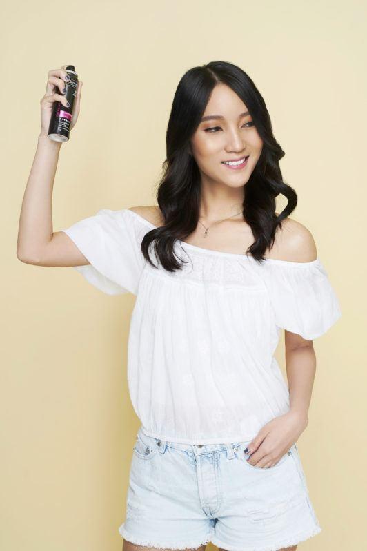 Wanita asia dengan model rambut beach waves dengan warna rambut hitam sedang menyemprotkan hairspray