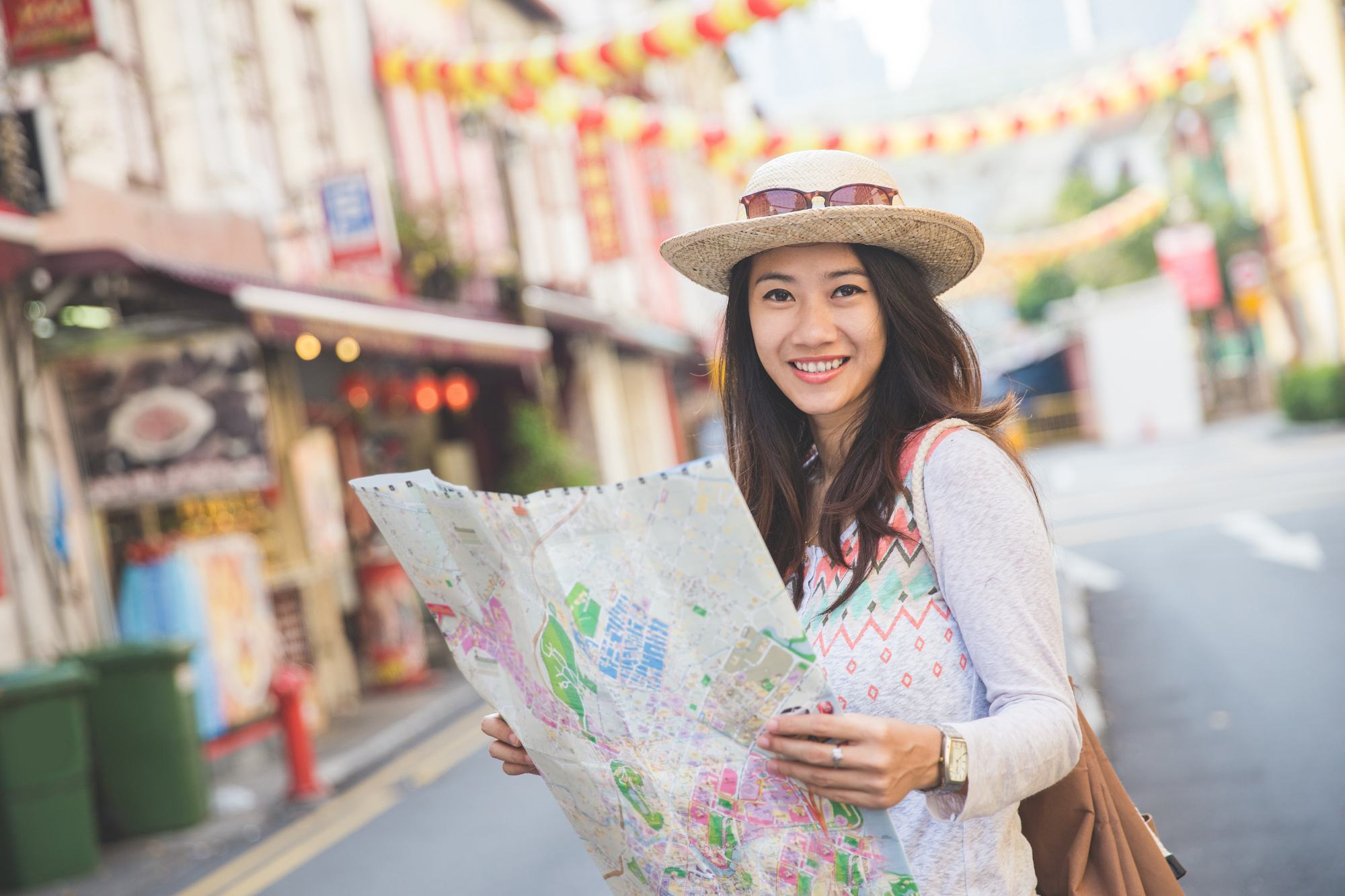 Wanita asia dengan rambut cokelat model rambut layer topi dengan kacamata memegang peta untuk traveling