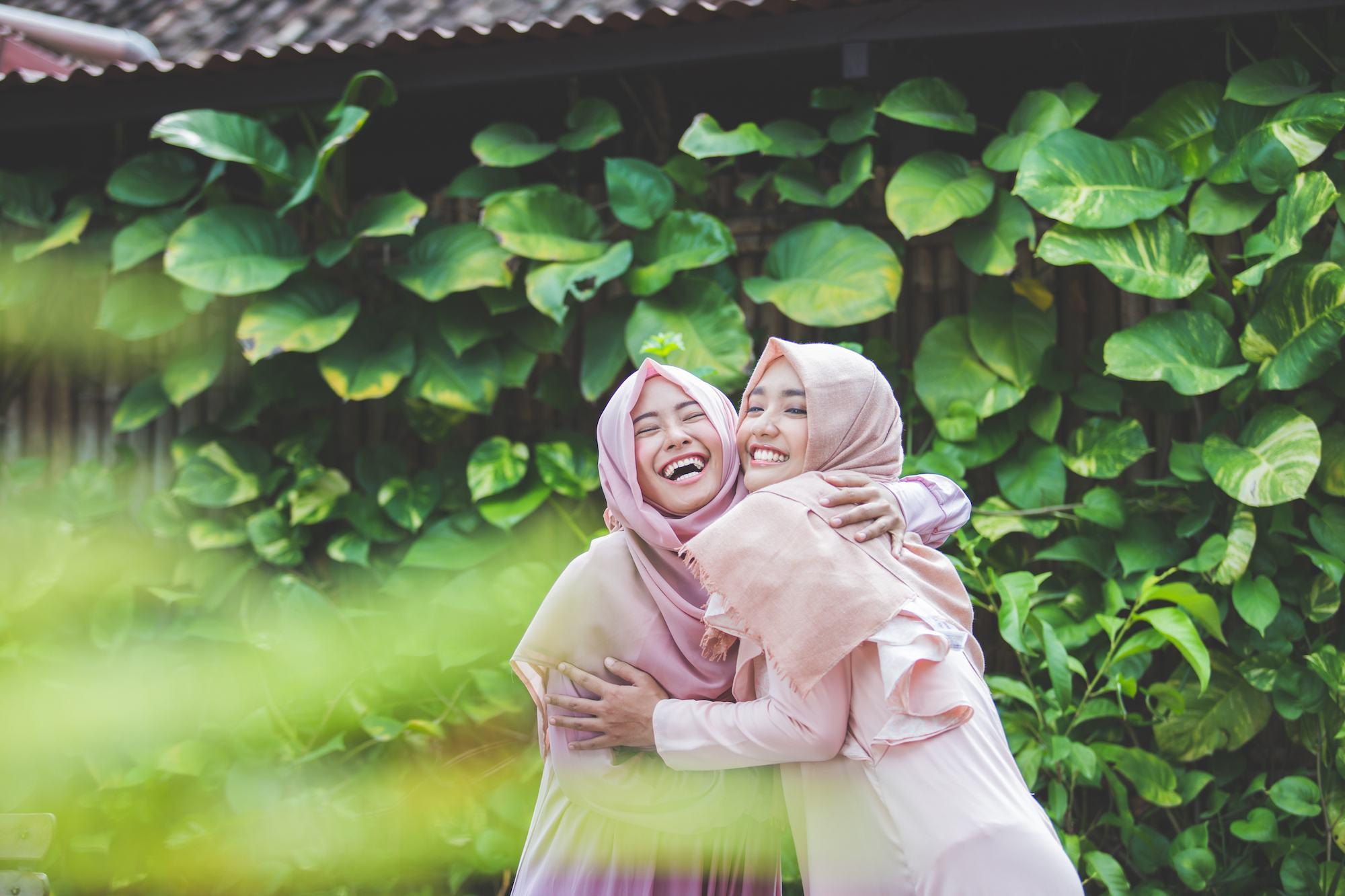 Dua wanita asia dengan hijab pink dan baju pink sedang berpelukan di taman