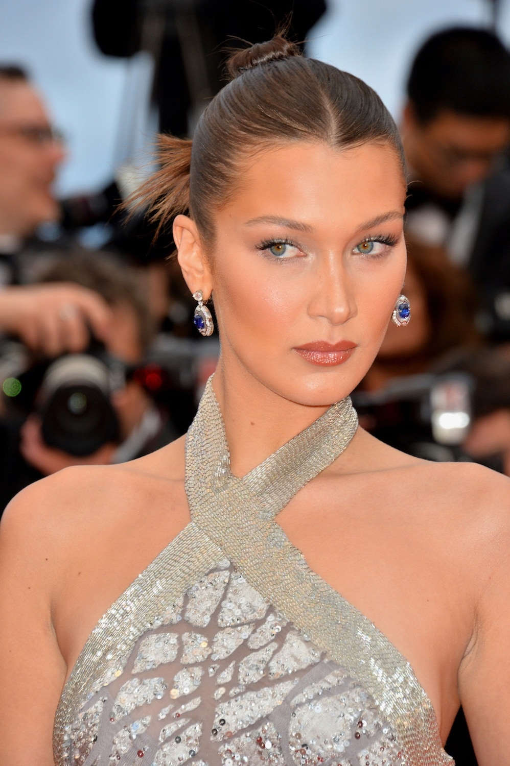 Gaya rambut sleek top knot dengan gaya messy Bella Hadid Cannes Film Festival 2018.