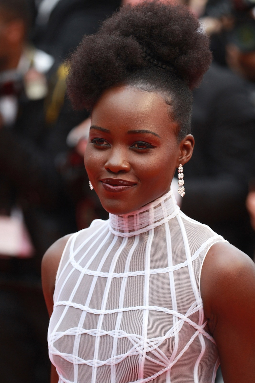Lupita Nyong'o dengan model rambut braided updo faux hawk.