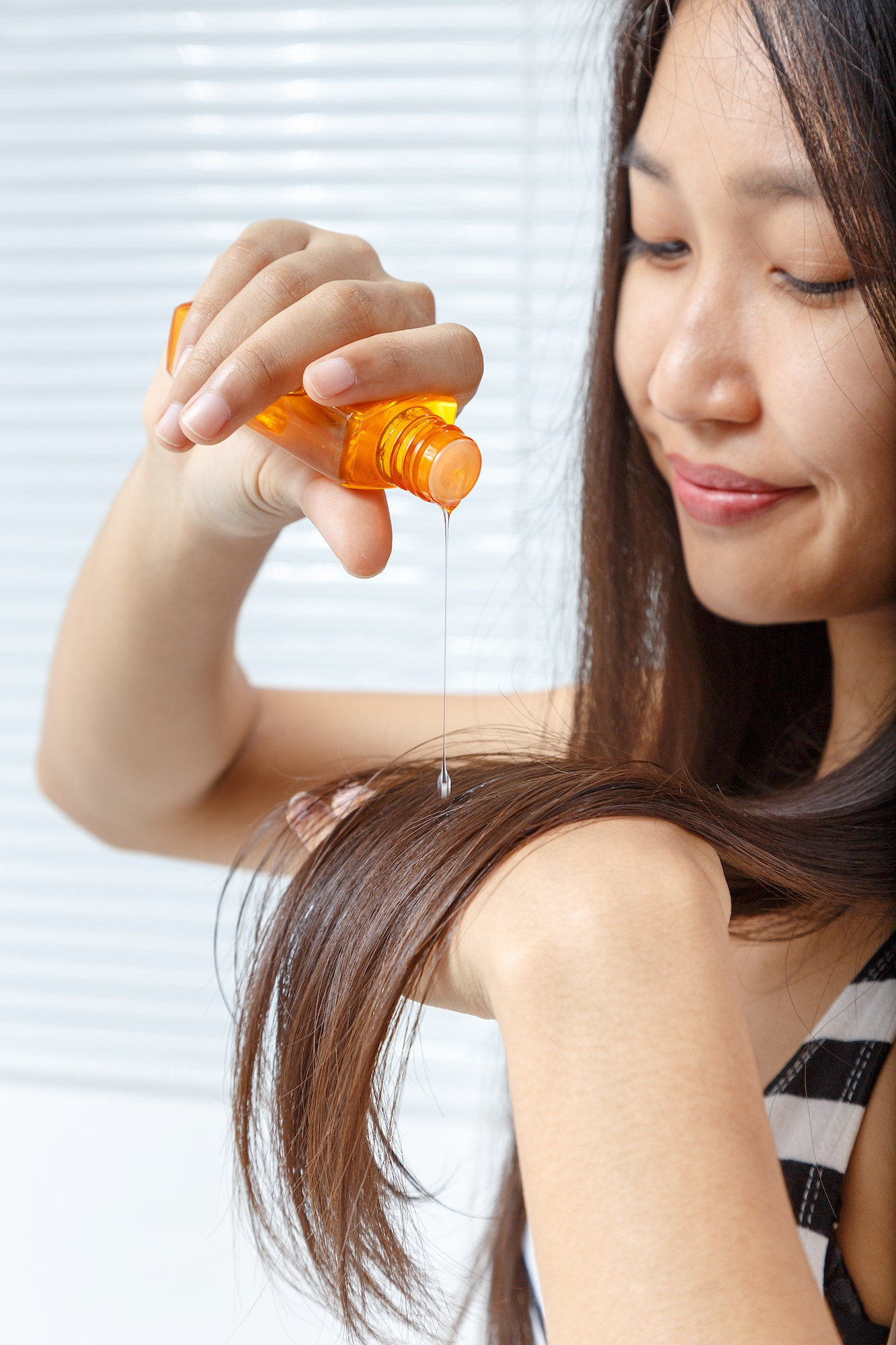Wanita asia dengan rambut panjang menggunakan hair oil