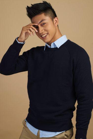 Pria asia dengan model rambut faux gawk dan sweater hitam kemeja biru