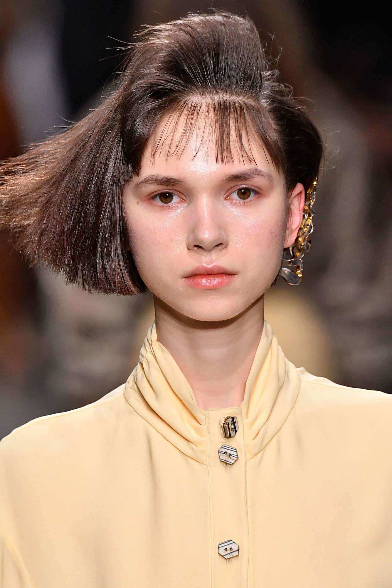 gaya rambut 80an model bob dengan poni disisir ke atas.