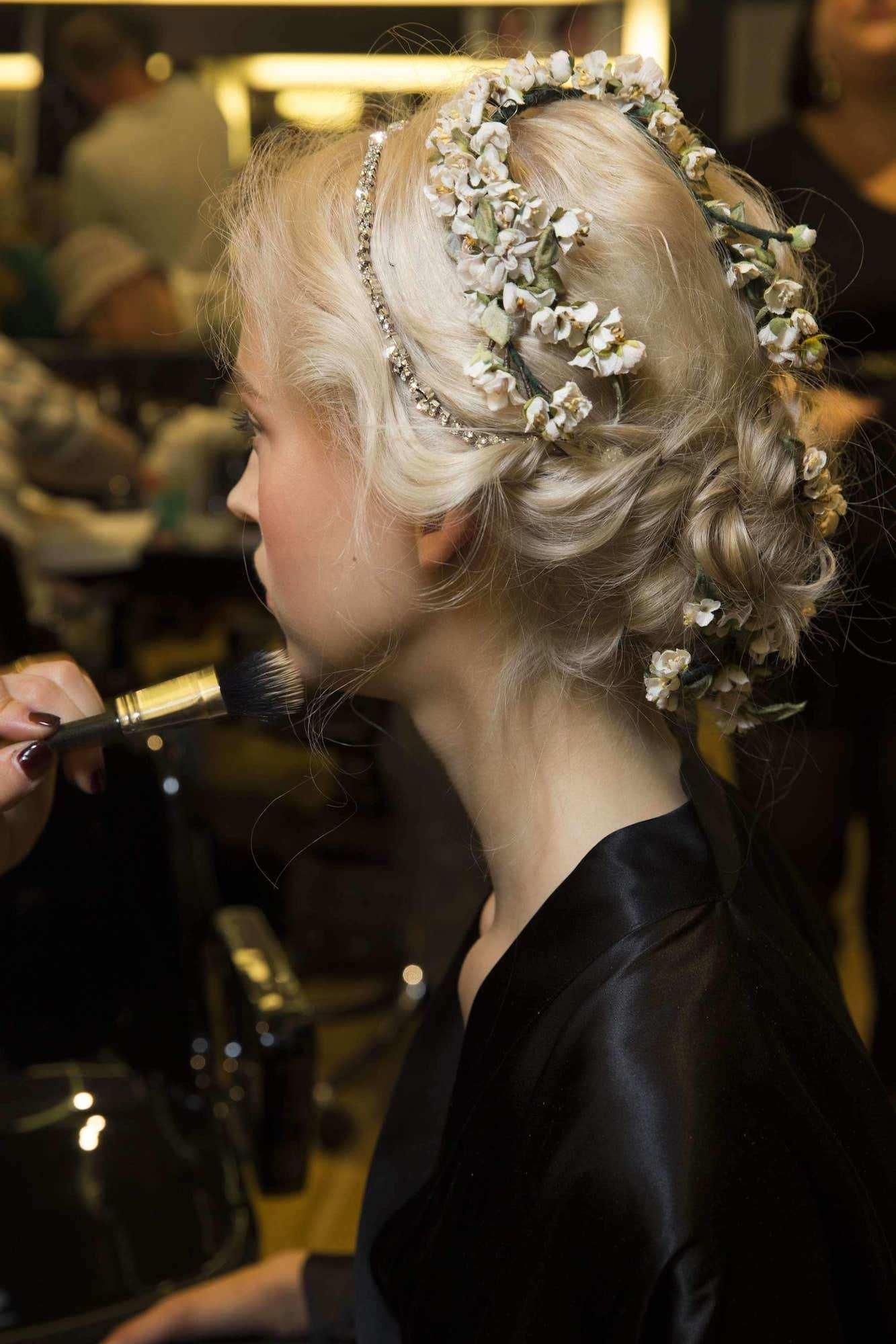 Low bun dengan model rambut yunani dengan aksesoris bunga.