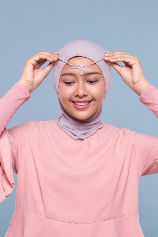 Wanita asia menggunakan ciput meletakkan aksesori pada hijabnya.