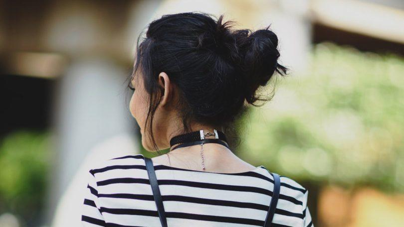 Wanita asia dengan rambut hitam menggunakan model rambut messy bun untuk rambut panjang