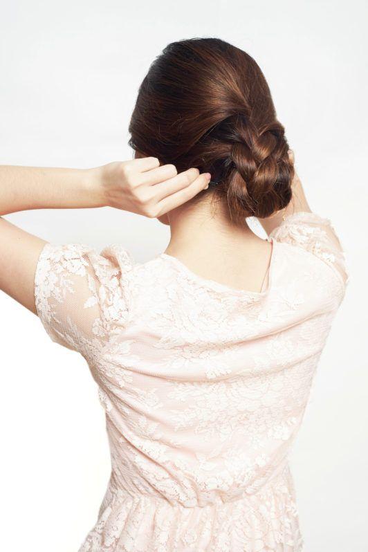 Wanita asia membentung sanggul kepang pada rambutnya.