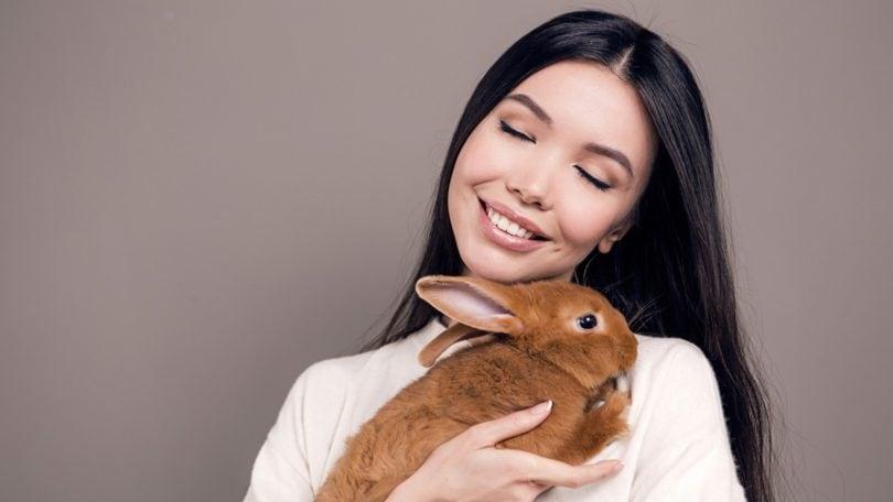 Wanita asia dengan rambut panjang lurus hitam memeluk kelinci cokelat