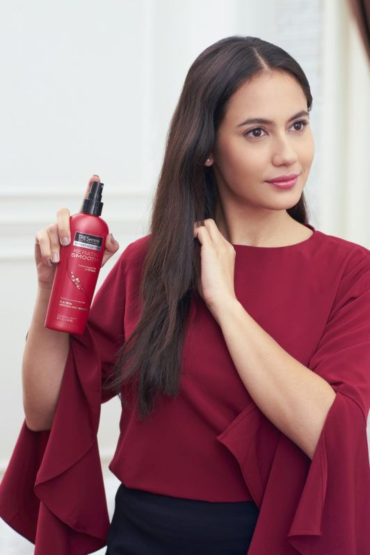 Pevita Pearce menyemprotkan rambut heat protection pada rambut menggunakan baju merah