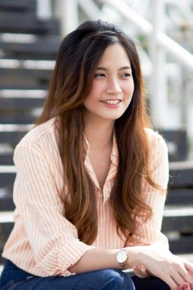Wanita asia dengan rambut panjang ombre cokelat duduk di bawah tangga